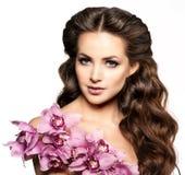 Giovane donna di bellezza, capelli ricci lunghi di lusso con il fiore dell'orchidea H Immagine Stock