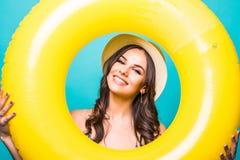 Giovane donna di bellezza in cappello di paglia e dello swimwear con l'anello gonfiabile giallo isolato su fondo verde immagini stock libere da diritti