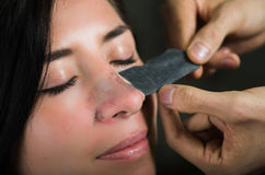 Giovane donna di bellezza che decolla una maschera nera del naso per liberare pelle dai punti neri Fotografia Stock