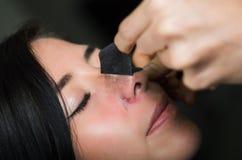Giovane donna di bellezza che decolla una maschera nera del naso per liberare pelle dai punti neri Immagine Stock