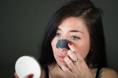 Giovane donna di bellezza che esamina specchio aplying una maschera nera del naso per liberare pelle dai punti neri Fotografia Stock Libera da Diritti