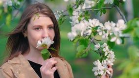 Giovane donna di bellezza che gode della natura nel meleto di primavera, bella ragazza felice in giardino con gli alberi di fiori archivi video