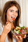 Giovane donna di bellezza che mangia insalata Fotografie Stock Libere da Diritti