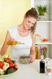 Giovane donna di bellezza che produce l'insalata dei germogli Immagine Stock