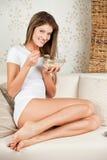 Giovane donna di bellezza che si siede sul sofà e che mangia cereale Fotografia Stock Libera da Diritti