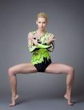Giovane donna di bellezza come basamento del gymnast sulle spaccature Immagini Stock Libere da Diritti