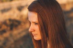 Giovane donna di bellezza con capelli rossi nel campo dorato al tramonto Immagini Stock