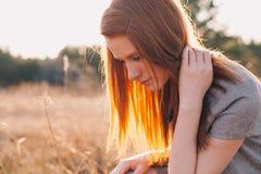Giovane donna di bellezza con capelli rossi nel campo dorato al tramonto Immagine Stock Libera da Diritti