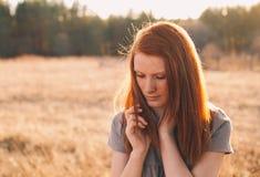 Giovane donna di bellezza con capelli rossi nel campo dorato al tramonto Fotografie Stock Libere da Diritti