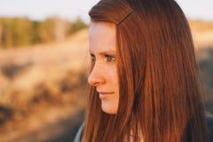 Giovane donna di bellezza con capelli rossi nel campo dorato al tramonto Immagine Stock