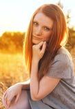 Giovane donna di bellezza con capelli rossi nel campo dorato al tramonto Fotografie Stock