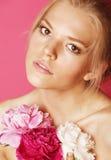 Giovane donna di bellezza con del fiore della peonia di rosa del primo piano di trucco lo sguardo delicato dell'offerta delicatam Immagine Stock