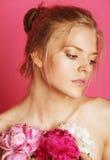 Giovane donna di bellezza con del fiore della peonia di rosa del primo piano di trucco lo sguardo delicato dell'offerta delicatam Fotografie Stock