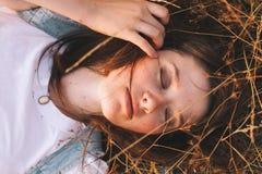 Giovane donna di bellezza con i capelli di Brown nel campo dorato al tramonto Immagine Stock