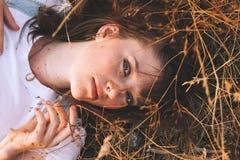Giovane donna di bellezza con i capelli di Brown nel campo dorato al tramonto Fotografia Stock