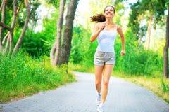 Giovane donna di bellezza con le cuffie che corre nel parco immagini stock libere da diritti
