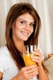 Giovane donna di bellezza con un vetro del succo di arancia Immagine Stock