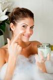 Giovane donna di bellezza nel bagno usando la maschera di protezione Fotografie Stock