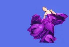 Giovane donna di bellezza in vestito lilla d'ondeggiamento Fotografia Stock Libera da Diritti
