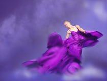 Giovane donna di bellezza in vestito lilla d'ondeggiamento Fotografie Stock