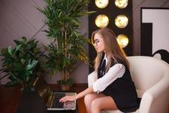 Giovane donna di bellezza in vetri che collocano nell'ufficio con il computer portatile Piante sui precedenti Affare e istruzione Immagini Stock