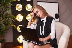 Giovane donna di bellezza in vetri che collocano nell'ufficio con il computer portatile Piante sui precedenti Affare e istruzione Fotografie Stock Libere da Diritti