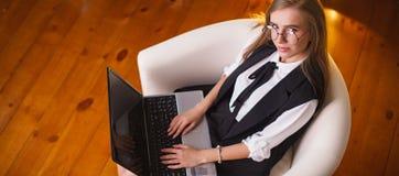 Giovane donna di bellezza in vetri che collocano nell'ufficio con il computer portatile Vista alla parte superiore Affare e istru Fotografia Stock Libera da Diritti