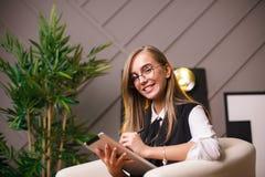 Giovane donna di bellezza in vetri che collocano nell'ufficio con la compressa Piante sui precedenti Affare e istruzione Fotografie Stock Libere da Diritti