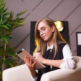 Giovane donna di bellezza in vetri che collocano nell'ufficio con la compressa Piante sui precedenti Affare e istruzione Immagini Stock Libere da Diritti