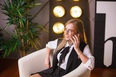 Giovane donna di bellezza in vetri che collocano nell'ufficio e che parlano sul telefono Piante sui precedenti Affare e Immagini Stock Libere da Diritti