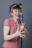 Giovane donna di canto che esegue con il retro micro Fotografie Stock
