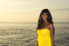 Giovane donna di colore afroamericana attraente ed affascinante nella posa elegante ed elegante del vestito da estate rilassata s Immagini Stock Libere da Diritti
