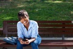 Giovane donna di colore attraente che si siede sul banco fuori con il telefono cellulare Fotografie Stock