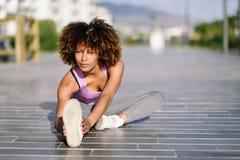 Giovane donna di colore che fa allungamento dopo avere corso all'aperto Immagine Stock Libera da Diritti