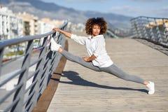 Giovane donna di colore che fa allungamento dopo avere corso all'aperto Immagini Stock