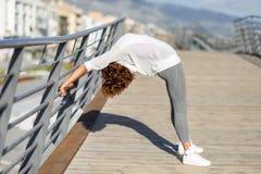 Giovane donna di colore che fa allungamento dopo avere corso all'aperto Fotografia Stock