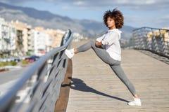 Giovane donna di colore che fa allungamento dopo avere corso all'aperto Fotografie Stock