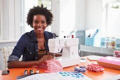 Giovane donna di colore che usando una macchina per cucire che guarda alla macchina fotografica Immagine Stock Libera da Diritti