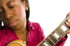 Giovane donna di colore ispanica che gioca chitarra elettrica fotografia stock libera da diritti