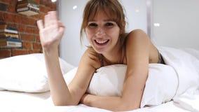 Giovane donna di conversazione che si trova a letto, video chiacchierata online, vista del webcam fotografia stock