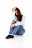Giovane donna di depressione che si siede sul pavimento Fotografie Stock Libere da Diritti