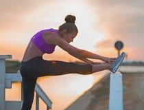 Giovane donna di forma fisica che allunga all'aperto nella sera Immagini Stock Libere da Diritti