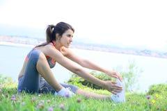 Giovane donna di forma fisica che allunga dalla spiaggia Immagine Stock