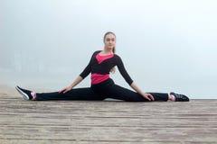 Giovane donna di forma fisica che allunga durante l'allenamento di addestramento all'aperto Fotografia Stock Libera da Diritti