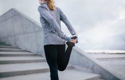 Giovane donna di forma fisica che allunga la sua gamba Fotografie Stock Libere da Diritti