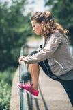 Giovane donna di forma fisica che allunga nel parco della città Fotografia Stock