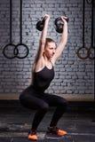 Giovane donna di forma fisica che fa allenamento del crossfit con kettlebell contro il muro di mattoni Fotografia Stock Libera da Diritti
