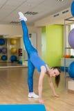 Giovane donna di forma fisica che fa allungamento alla palestra Fotografia Stock