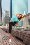 Giovane donna di forma fisica che fa esercizio spaccato stante sulla via della città Ragazza sportiva di misura che risolve all'a Fotografia Stock