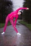 Giovane donna di forma fisica che fa esercizio un giorno piovoso Immagini Stock